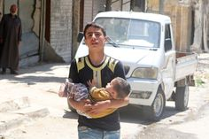 Boy carries baby in Aleppo violence