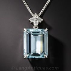 A cool swimming pool blue emerald cut aquamarine, weighing 11.54 carat, glistens, glows and swings to and fro below a sparkling quartet of bright white round brilliant-cut diamonds, all of which are presented in gleaming platinum. The pendant,measuring just shy of 1 inch by 1/2 inch, suspends from an 18 inch platinum chain.