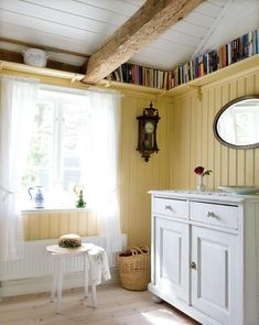 Room in a Swedish summer house, butter yellow walls, shelf of books running under ceiling - love the yellow and white, and the pretty curtains Small Space Living, Small Spaces, Ceiling Shelves, Ceiling Beams, Tall Ceilings, Swedish House, Yellow Walls, Coups, Home Interior Design
