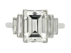 Art Deco diamond ring, circa 1935. Set to centre with a rectangle step cut diamond with a weight of 2.62 carats, I colour, VS2 clarity, in an open back corner claw setting, flanked by four vertically set rectangle baguette cut diamonds in open back rubover settings with an approximate combined weight of 0.50 carats. The total approximate diamond weight is 3.12 carats, all to a tapered step down form with elegant scrolled openwork to the linear conforming gallery with square backholing…
