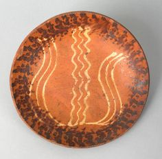 """Pook & Pook.  April 20th & 21st 2007. Lot 540.  Estimated: $1500 - $2500. Realized Price: $4914. Pennsylvania, Dryville Area, redware plate, early 19th c., with 3 line yellow slip tulip surrounded by a black manganese sponged rim, 10 1/4"""" dia. For a nearly identical example, see the collection of Walter Himmelreich Collection, May 1973, lot 43. Provenance: Walter Himmelreich, 1958 Pennypacker Auction."""