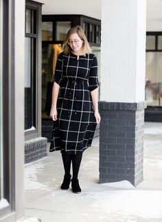 Woman wearing a modest black and white windowpane style midi dress. This dress has a fabric self tie, elastic waist and sleeves. It is also paired with black tights and black booties. Tights And Heels, Black Tights, Black Booties, Modest Dresses, Tight Dresses, Short Sleeve Dresses, Sneakers Street Style, Wearing Black, Dress Patterns