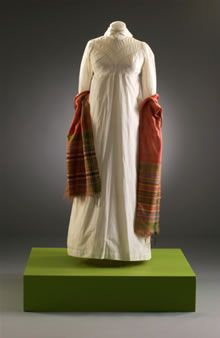 White cotton day dress, English, c. 1813. The sleeves are very long and are meant to be worn so that the cotton is pushed up the arm in soft folds. This image shows the dress worn with a rectangular shawl of dark pink woven wool with a striped design at either end. Shawls of light wool or silk were also worn by most women in the early 19th century. At this date they tended to be rectangular rather than square.