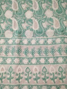White fabric with green chikan hand embroidery, applique and net work. It has all over jaal work and motifs at the back. Third image is of sleeves. Bottom and Dupatta not included. Fabric:Cotton Length: 45 inches Sleeves Style:Full Sleeves with motifs and border Technique :Hand and Machine Embroidery Wash Care :Hand Wash or dryclean  Since it is a hand crafted product,there can be slight variations in the embroidery. Actual colours may va