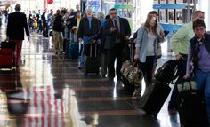 This photo shows travelers waiting in line at the airport. It looks pretty crowded.