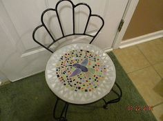 I bought this little metal chair at the flea market for a few bucks because it was missing the seat. My husband cut one out of some plywood and sanded it down. I cut the humming bird from a piece of irridized  stained glass for the center and surrounded it with little pieces of various colored glass and then finished it off with light gray grout. I think it would be cute used as a stand for a small plant