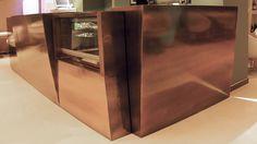 BRONZE, bancone cocktail lounge bar per il locale dei tuoi sogni. Si distingue dagli altri sia per la sua forma irregolare del top e del frontale, sia per la colorazione effetto bronzato invecchiato. Puo' essere richiesto in finitura lucida e in finitura opaca, le misure e i colori sono personalizzabili. La protezione ceramica lo garantisce nel tempo. E' realizzato in Adamantx® 100% made in Italy.
