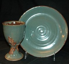 This wheel thrown pottery communion set is handmade in stoneware. The chalice is thrown in two parts to allow for a hollow stem (making it a bit lighter and dishwasher safe). It is glazed in the Mossy Bark Series...shades of moss green and mahogany brown.  The chalice holds 1 & 1/2 cups to rim and measures 7 to 8 inches tall and approximately 3 & 1/2 inches wide. The paten is 9 inches across and 1 inch tall. Oak leaves stained a deep brown adorn the stem.  Engraved as per in...