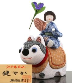 A kimekomi Gogatsu ningyou set consisting of a boy with a sweet flag flower (a symbol of Children's Day/Boys' Day due to its sword-like appearance) and a dog modeled after a hariko inu (a dog-shaped papier mache ornament believed to promote safe...