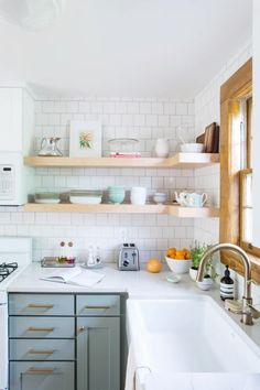 Mint green kitchen cabinets under neutral open kitchen shelves with white tiles against splashes … – White N Black Kitchen Cabinets Mint Green Kitchen, Green Kitchen Cabinets, Kitchen Shelves, Kitchen Dining, Kitchen White, Kitchen Corner, White Cabinets, Country Kitchen, Kitchen Storage