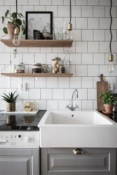 Grey kitchen with open shelves and lightbulb pendants