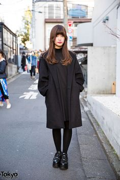 Kurumi on the street in Harajuku wearing a wool coat from Fig&Viper with a Jouetie dress, M.Y.O.B. sackpack, and Yosuke platform sneakers.