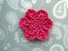 Two rounds of sc (UK dc) followed by the petals, each made on their own length of 19 chain! You pick up loops from the chain, then pull your yarn through the lot and end up with one petal, then repeat round the circle… and this is what you end up with :)