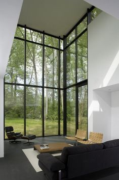 Open and airy interior living room with large, oversized windows with black frames