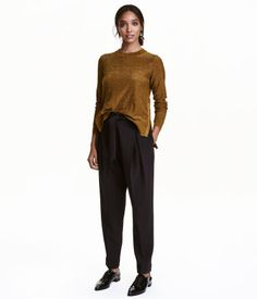 Black. Pants in woven fabric with a hook-and-eye fastener, pleats at top, and side pockets. Dropped gusset and wide, tapered legs with sewn cuffs at hems.