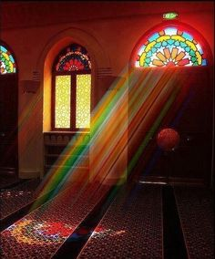Beautiful rainbow reflections inside a Moroccan mosque. Notice that the pattern used in the glass is the standard Moroccan zellige motif. Pretty.