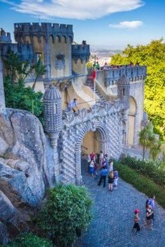 Tourists enter Sintra's Pena palace through a stone archway and over a small drawbridge with the colourful castle in the background - Sintra, Portugal