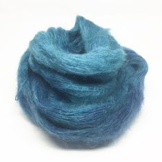 This is a lovely, fluffy blend is sheeny silk and hazy kid mohair. It's delicate and light to knit with, and make a fluffy, open fabric. I've also used it as weft in my weaving, and it adds a really lovely halo effect.This colourway is a deep, greeny-blue with turquoise highlights. The blend is:70% kid mohair / 30% silkIt is laceweight yarn, and each 50g skein is approximately 420m.