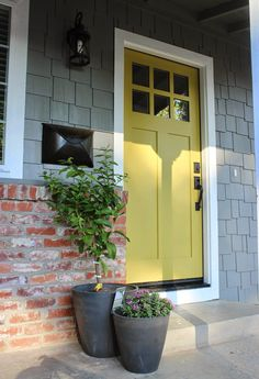 exterior is Pier by Behr, trim is Ultra White Sherwin Williams paint and front door is a shade of chartreuse Antiquity by Sherwin Williams