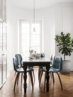 gorgeous Scandinavian style dining room with light blue chairs, vintage table, and white walls, a plant, large window, and herringbone floors // H&M Home's Head Of Design Proves Why You Should Only Live With Things You Love