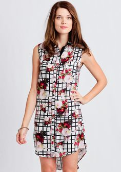 Complete with a button-up front and classic collar, this enticing white dress is designed with a black grid pattern adorned with a bold floral print.