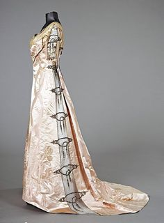 A Worth ball gown (circa 1910, with signature label to waistband, of pink damask satin woven with large bearded irises and swags of interlaced ribbons, the side panels and sleeves inset with tulle panels embroidered in metal threads and diamanté studs
