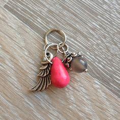 Bedel van roze howliet druppel, 8mm grijs agaat met metalen sierkap uit India en een metalen vleugel. Van JuudsBoetiek, €5,50. Te bestellen op www.juudsboetiek.nl.