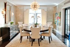 Classic but not old-fashioned. Round table in a rectangular dining room. Colorful LARGE artwork, equally large mirror with sconces.