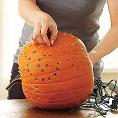 Twinkle light pumpkin...sooo doing this!! Drill + lights.