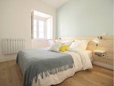 Modern, minimal bedroom with wooden floorboards, wooden headboard and teal throw rug. Apartamento da Glória by Homestories.