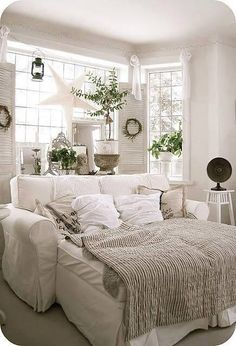 A feeling of an ocean front cottage with the white window frames, wooden blinds and just a sprinkle of green make for a peaceful environment.... Love the large sofa and quirky trinkets