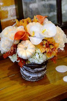 Arrangement with white orchids, white pumpkins, orange calla lilies and orchids.