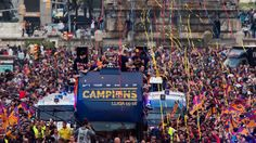 FC Barcelona players celebrate on an open top bus during their victory parade after winning the Spanish La Liga on May 15, 2016 in Barcelona.