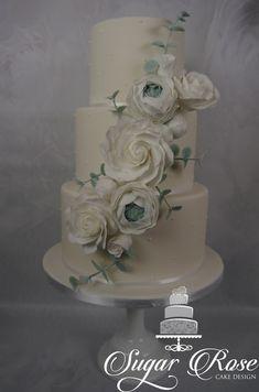 3 tier white wedding cake with white sugar roses and eucalyptus