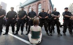 A protester sits in front of Chicago police officers Saturday during a demonstration on State street