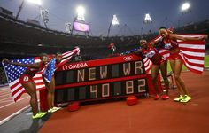 Members of the U.S. team pose with their national flags after winning the women's 4x100m relay final during the London 2012 Olympic Games