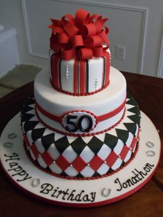 Horse Racing Silks inspired 50th Birthday cake - This was for a gentleman's 50th birthday party.  He is a big horse racing fan and his wife surprised him with this cake.  She wanted something sophisticated and elegant using red, white and black with touches of silver.  I used some racing silks as inspiration for the patterns and added the dragees for a neat metallic touch. Large fondant loopy bow with tails.  There were also some horseshoes on the board which he likes and for good luck for…