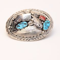 Old Pawn Kingman Turquoise and Coral Belt Buckle The traditional western craftsmanship of the amazing artist Lucky was beautifully displayed in this silver belt buckle represents Navajo craftsmanship at its finest. This piece of Native American jewelry highlights a rare, genuine bear claw featured in a silver overlay beautifully accented with sterling silver carefully hand crafted feathers with two Kingman turquoise and one coral cabochons. Belt buckle is stamped sterling and signed by the…