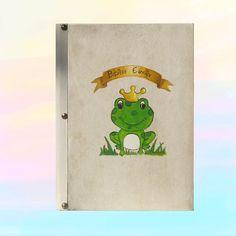 Χειροποίητο βιβλίο ευχών βάπτισης με ξύλινο εξώφυλλο (μπρος και πίσω) πάχους 6 χιλιοστών, δεμένο με δέρμα. Είναι διακοσμημένο με ζωγραφιά δια χειρός (πρίγκιπας βάτραχος) και με μεταλλικά στοιχεία
