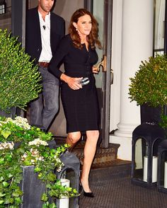 Caitlyn Jenner wears a belted black dress, a metallic clutch, and slingback pumps