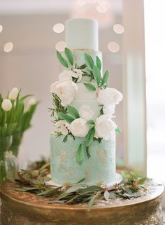 Mint coloured cake with white flowers and gold specks created by The Cake Whisperer