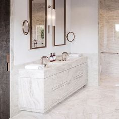 The full marble basin and drawer unit in the master bathroom of our Ireland project with sliding bronze vanity mirrors and a glimpse of the black velum doors #interiordesign #luxuryhomes #laurahammett
