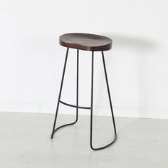 Gavin Counter Stool. Enjoy the simple, geometric architecture of this industrial modern stool whether you're appreciating the way the lines accentuate a kitchen island or poised on the solid mango contoured seat. Tube-shaped black iron legs create an attractive continuous look in a barstool where form exquisitely follows function.