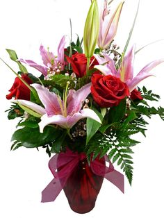 """Give your sweetie a gorgeous vase of red roses and lilies this Valentines. A red glass vase is arranged with 8 red roses and 2 stems of pink oriental lilies and accented with wax flower. Height: 22""""  Width: 12""""  I just want you, that's  all. all you  flaws,  mistakes,  smiles,  giggles,  jokes,  sarcasm.  everything.  I just want you."""