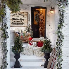 """A holiday winter wonderland courtesy of Romabio Classico Limewash paint, and one of our favorites, @kindredvintage """"One week until Christmas and we are so excited to show you our front porch reveal with @grandinroad!! The planters, the garland, the chair and wreath... all from @grandinroad! ✨what are you looking forward to most this last week before Christmas?! For us, relaxing with these two is on the tippy top of our list. ❤️ sign by @harpergrayce, blankets by @colorwaysgallery 