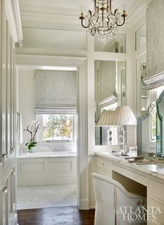 """The master suite is awash in soothing hues. """"The previous master was choppy, so existing space was absorbed into the new master when the wings were added,"""" says Izlar. The Panache Designs chandelier and Cameron vanity chair are through Ainsworth-Noah. The 19th-century Italian commode is from Parc Monceau."""