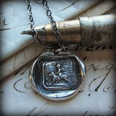 "The French motto "" La Fidelite me conduit"" surrounds this sweet charm picturing a cherub riding the back of a Spaniel."