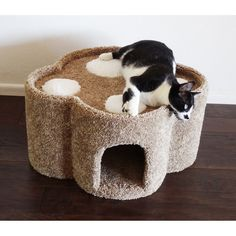 This paw-shaped cat condo is a perfect place for cats to play or relax. The condo features plush carpeting that is available in five color options, a cave, a sturdy top with holes in the toes, and a heavy base that prevents tipping.