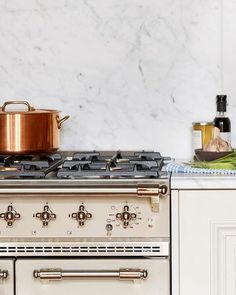 The snow is coming down in NY and we are thinking about simmering some stew on the stove. If only we had this gorgeous French @lacanche_us range, on trend marble slab backsplash, and satin brass hardware  // design by @abkasha // #frenchstyle #kitchentrends #timetoeat