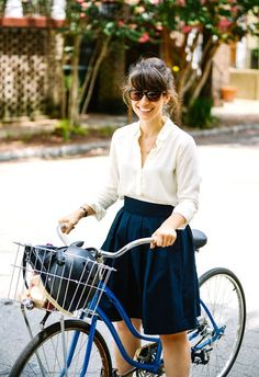 Women's street style: Classic shirt, skirt, simple jewelry + watch. Cobalt bicycle.
